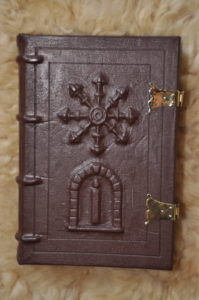leather-bound book with escarbuncle and arch with candle