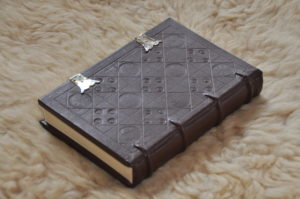 leather-bound book with stamped squares and escarbuncles
